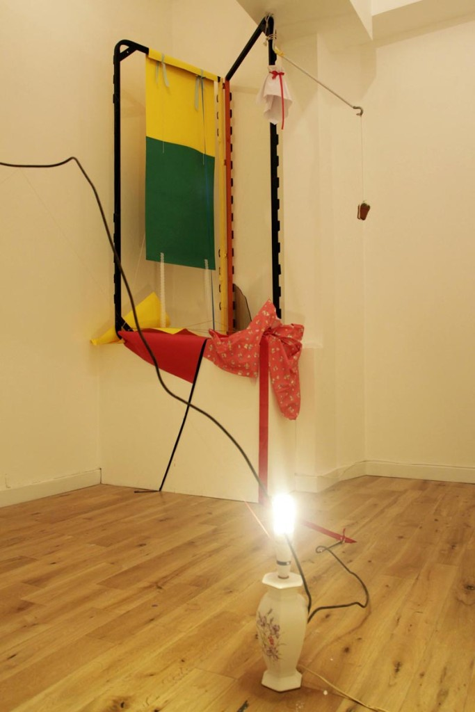 Stephanie Burt. Miss McCraw Loses Her Skirt At Hanging Rock, 2015. Baby shoes, lamp, cactus, metal wire, ribbon, cloth, lace, string, paper, metal.